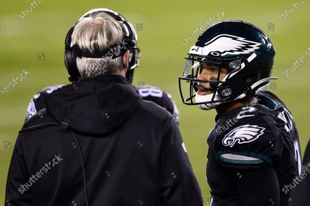 Philadelphia Eagles' Jalen Hurts, right, talks with Doug Pederson during the first half of an NFL football game against the New Orleans Saints, in Philadelphia