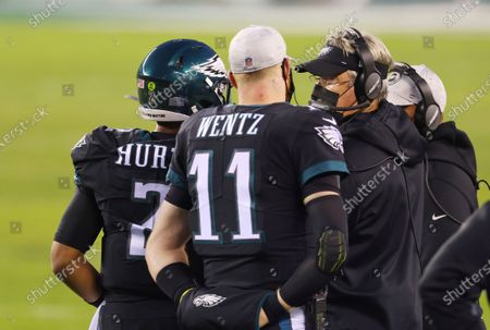 Philadelphia Eagles' head coach Doug Pederson talks with quarterback Jalen Hurts (2) and Carson Wentz (11) during an NFL football game against the New Orleans Saints, in Philadelphia