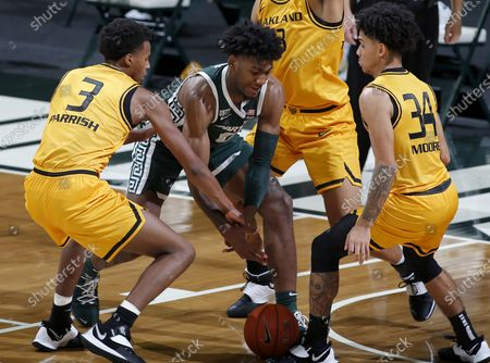 Michigan State's Aaron Henry, center and Oakland's Micah Parrish, left, and Jalen Moore, right, vie for the ball during an NCAA college basketball game, in East Lansing, Mich. Michigan State won 109-91