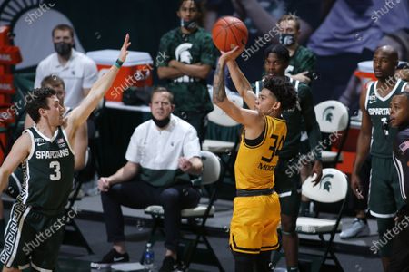 Stock Picture of Oakland's Jalen Moore, right, shoots against Michigan State's Foster Loyer (3) during an NCAA college basketball game, in East Lansing, Mich. Michigan State won 109-91