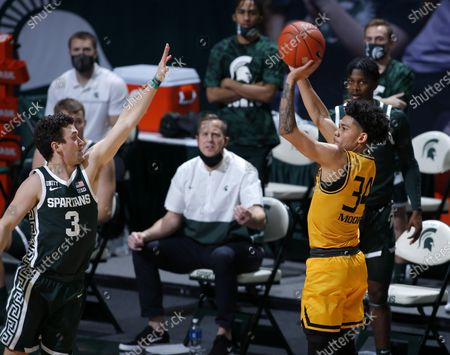 Oakland's Jalen Moore, right, shoots against Michigan State's Foster Loyer during an NCAA college basketball game, in East Lansing, Mich. Michigan State won 109-91
