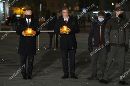 Polish President Andrzej Duda (L) holds a candle as he marks the 39th anniversary of the imposition of martial law in Poland in a special address on Warsaw's Pilsudskiego Square, Warsaw, Poland, 13 December 2020. Poland's communist government imposed martial law on 13 December 1981, in a bid to quell the rising Solidarity trade union. At least 91 people were killed during the martial law period that ended on 22 July 1983.