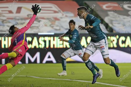Pumas' goalkeeper Alfredo Talavera, left, dives and makes a save from Leon's Emmanuel Gigliotti during their Mexican soccer league second-leg final match in Leon, Mexico
