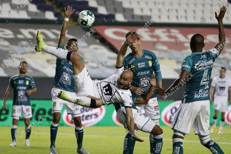 Pumas' Carlos Gonzalez, center, falls down in a clash with Leon's Pedro Aquino during their Mexican soccer league second-leg final match in Leon, Mexico