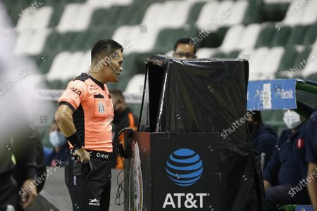 Referee Jorge Perez Duran checks the Video Assistant Referee (VAR) during the Mexican soccer league second-leg final match between Leon and Pumas, in Leon, Mexico