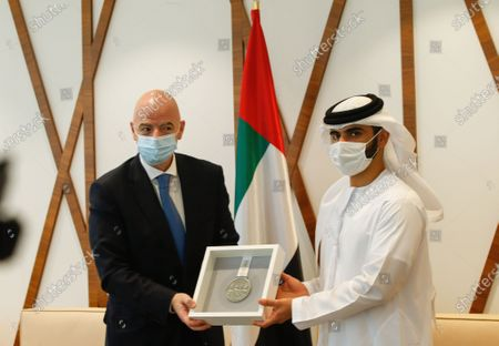 Stock Photo of FIFA President Gianni Infantino (L) receives the shield of the Dubai Sports Council from Sheikh Mansour bin Mohammed bin Rashid Al Maktoum (R), Chairman of Dubai Supreme Committee of Crisis and Disaster Management during his visit in Dubai, United Arab Emirates, 14 December 2020.