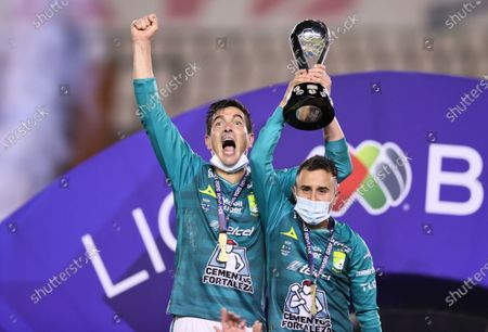 Stock Picture of Leon's Juan Gonzalez (L) and Luis Montes celebrate with the trophy after the second leg of the final of the 2020 Liga MX Guardianes tournament against UNAM Pumas in Leon, Mexico, on Dec. 13, 2020. (Xinhua/Carlos Ramirez/Straffon Images)