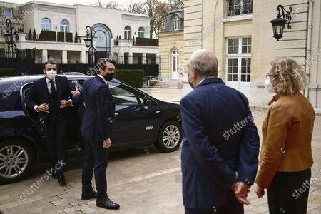 French President Emmanuel Macron, left, is welcomed by OECD's Secretary General Angel Gurria, second right, and France's representative at the OECD Muriel Penicaud, right, as he arrives for a ceremony marking the 60th anniversary of the creation of the Organisation for Economic Co-operation and Development (OECD), at its headquarters in Paris