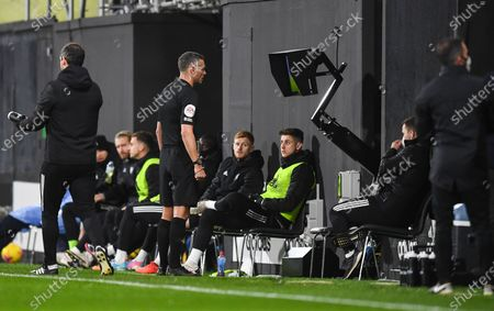 Referee Andre Marriner looks at VAR