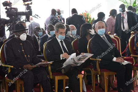 Former French President Nicolas Sarkozy, center, former Nigerian President Goodluck Jonathan, left, and French minister of foreign affairs Jean-Yves Le Drian attend Ivorian President Alassane Ouattara's inauguration in Abidjan, Ivory Coast, . Ouattara, who received some 94.3% percent of the vote, had been expected to easily win the election after the leading opposition figures called on their supporters to stay home