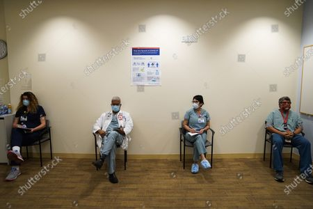 Nurse Kim Taylor, from left, Dr. Brian Thompson, housekeeping assistant Angela Balam and respiratory care practitioner Raul Aguilar wait in a holding room after receiving he Pfizer-BioNTech COVID-19 vaccine at Kaiser Permanente Los Angeles Medical Center in Los Angeles