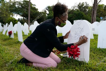 "Stock Image of Rachel Moore writes a tribute to her cousin Wilton ""Bud"" Mitchell who died of COVID-19 at a symbolic cemetery created to remember and honor lives lost to COVID-19, in the Liberty City neighborhood of Miami. The U.S. death toll from the coronavirus topped 300,000 Monday, Dec. 14, just as the country began dispensing COVID-19 shots in a monumental campaign to conquer the outbreak"