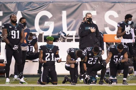 Stock Photo of Philadelphia Eagles safety Jalen Mills (21), cornerback Darius Slay (24), safety Rodney McLeod (23) and linebacker Shaun Bradley (54) kneel for the National Anthem prior to the NFL football game against the New Orleans Saints, in Philadelphia