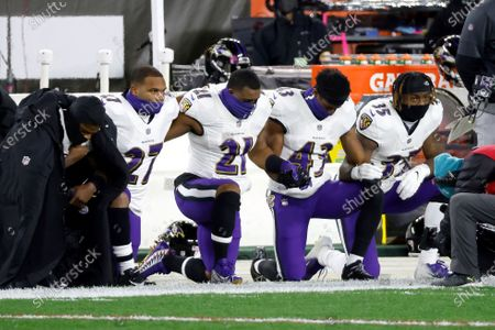 Baltimore Ravens quarterback Lamar Jackson (8), running back J.K. Dobbins (27), running back Mark Ingram II (21), running back Justice Hill (43), and running back Gus Edwards (35) kneel during the playing of the national anthem prior to the start of an NFL football game against the Cleveland Browns, in Cleveland