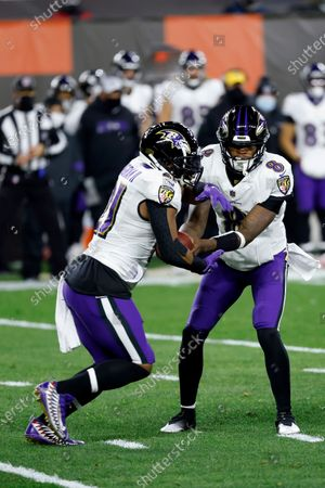 Stock Photo of Baltimore Ravens quarterback Lamar Jackson (8) hands the ball off to running back Mark Ingram II (21) during an NFL football game against the Cleveland Browns, in Cleveland