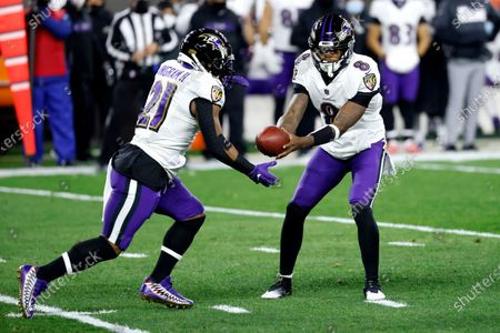Baltimore Ravens quarterback Lamar Jackson (8) hands the ball off to running back Mark Ingram II (21) during an NFL football game against the Cleveland Browns, in Cleveland