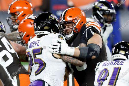 Cleveland Browns guard Joel Bitonio (75) blocks Baltimore Ravens defensive end Derek Wolfe (95) during an NFL football game, in Cleveland