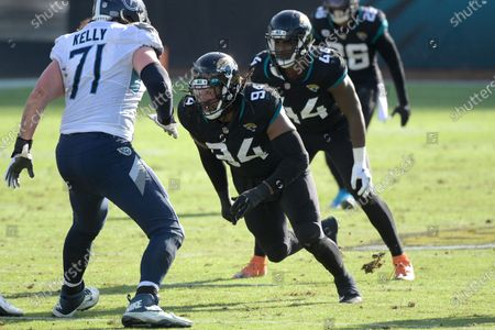 Tennessee Titans offensive tackle Dennis Kelly (71) sets up to block against Jacksonville Jaguars defensive end Dawuane Smoot (94) during the first half of an NFL football game, in Jacksonville, Fla