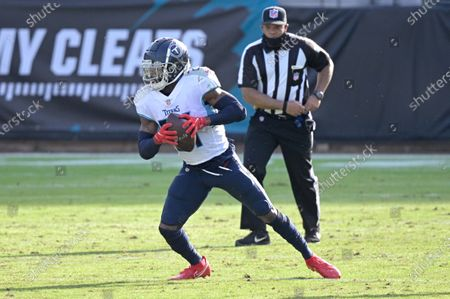 Tennessee Titans cornerback Malcolm Butler (21) intercepts a pass during the second half of an NFL football game against the Jacksonville Jaguars, in Jacksonville, Fla