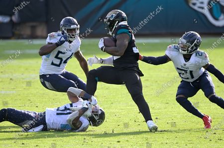 Jacksonville Jaguars running back James Robinson (30) is tackled by Tennessee Titans safety Kevin Byard (31), cornerback Malcolm Butler (21) and linebacker Rashaan Evans (54) after catching a short pass during the second half of an NFL football game, in Jacksonville, Fla