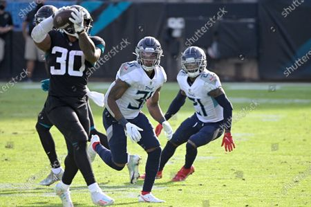 Tennessee Titans safety Kevin Byard (31) and cornerback Malcolm Butler (21) pursue as Jacksonville Jaguars running back James Robinson (30) catches a short pass during the second half of an NFL football game, in Jacksonville, Fla