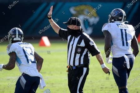 Umpire Paul King (121) works a play during the first half of an NFL football game between the Jacksonville Jaguars and the Tennessee Titans, in Jacksonville, Fla