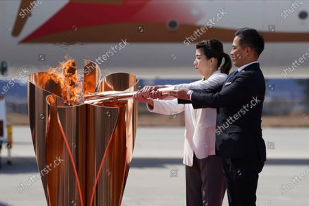 Stock Picture of Three-time Olympic gold medalists Tadahiro Nomura, right, and Saori Yoshida light the torch during Olympic Flame Arrival Ceremony at Japan Air Self-Defense Force Matsushima Base in Higashimatsushima in Miyagi Prefecture, north of Tokyo. The torch relay for the postponed Tokyo Olympics is to start in just over three months, and it faces the same questions as the Olympics about being held safely during the coronavirus pandemic