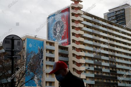 "Man walks past buildings, one decorated with a painting called ""Marianne"", symbol of the French Republic, by American artist Shepard Fairey, Tuesday Dec.15, 2020 in Paris. The painting has been defaced with white paint on the motto, red tears have been added and the art-piece has been renamed ""Marianne cries"