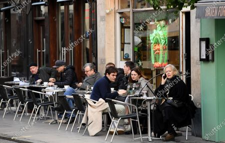 People sit outside in Soho in London, Britain, 15 December 2020. Britain's health secretary Matt Hancock has announced that London and its surrounding areas will be placed under  Tier 3 which is the toughest level in England's three-tier system. Londoners won't be able socialize indoors and bars, pubs and restaurants must close except for takeout.