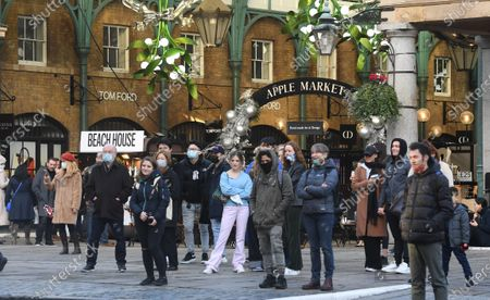 Stock Photo of Pedestrians in Covent Garden in London, Britain, 15 December 2020. Britain's health secretary Matt Hancock has announced that London and its surrounding areas will be placed under  Tier 3 which is the toughest level in England's three-tier system. Londoners won't be able socialize indoors and bars, pubs and restaurants must close except for takeout.