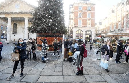 Stock Image of Pedestrians take pictures by fake snow in Covent Garden in London, Britain, 15 December 2020. Britain's health secretary Matt Hancock has announced that London and its surrounding areas will be placed under  Tier 3 which is the toughest level in England's three-tier system. Londoners won't be able socialize indoors and bars, pubs and restaurants must close except for takeout.