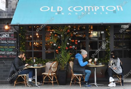 People sits for lunch in Soho in London, Britain, 15 December 2020. Britain's health secretary Matt Hancock has announced that London and its surrounding areas will be placed under  Tier 3 which is the toughest level in England's three-tier system. Londoners won't be able socialize indoors and bars, pubs and restaurants must close except for takeout.