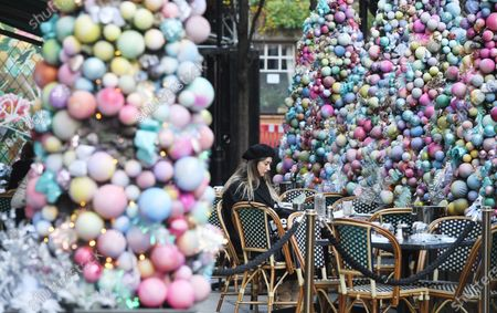 A woman sits on a cafe in London, Britain, 15 December 2020. Britain's health secretary Matt Hancock has announced that London and its surrounding areas will be placed under  Tier 3 which is the toughest level in England's three-tier system. Londoners won't be able socialize indoors and bars, pubs and restaurants must close except for takeout.