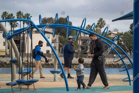 A man playing with a child prepares to put on his mask after being reminded of the city's rules by Long Beach's health ambassadors Chris Bonomo, center in blue jacket, who has had COVID-19 before and sees the importance in educating and reminding others to keep safe, and Pablo Razo, 18, left, at Mother's Beach in Long Beach Thursday, Dec. 10, 2020. The city hired 13 youth in partnership with Pacific Gateway Workforce Innovation Network in July to make sure people are following social distancing and mask mandates. They go around busy parks, beaches and streets, handing out masks to people. Long Beach City Council is considering ramping up enforcement for people who are not wearing masks and how it has been handling the pandemic lately, since the city has its own public health department, apart from LA County. The LBPD came under scrutiny recently after the Long Beach Post published a story showing pictures of a police training in early November where dozens of police officers were gathered close together, many not wearing masks. The community ambassadors reminded them about the safer at home order, bringing hand sanitizer, not to come to the park sick, maintain 6 feet distance with people outside of your household, anybody 2 years or older is required to wear a mask, wash hands frequently, and that nobody is allowed to gather with people outside of their household. (Allen J. Schaben / Los Angeles Times)