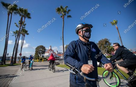 Bikers not wearing masks pass by Long Beach's health ambassadors Chris Bonomo, right center, who has had COVID-19 before and sees the importance in educating and reminding others, Ezequiel Gutierrez, 18, and Pablo Razo, 18, in background at left, check on the bike path to make sure people are complying with the current COVID-19 rules and restrictions at Shoreline Village in Long Beach Thursday, Dec. 10, 2020. The city hired 13 youth in partnership with Pacific Gateway Workforce Innovation Network in July to make sure people are following social distancing and mask mandates. They go around busy parks, beaches and streets, handing out masks to people. Long Beach City Council is considering ramping up enforcement for people who are not wearing masks and how it has been handling the pandemic lately, since the city has its own public health department, apart from LA County. The LBPD came under scrutiny recently after the Long Beach Post published a story showing pictures of a police training in early November where dozens of police officers were gathered close together, many not wearing masks. The community ambassadors reminded them about the safer at home order, bringing hand sanitizer, not to come to the park sick, maintain 6 feet distance with people outside of your household, anybody 2 years or older is required to wear a mask, wash hands frequently, and that nobody is allowed to gather with people outside of their household. (Allen J. Schaben / Los Angeles Times)