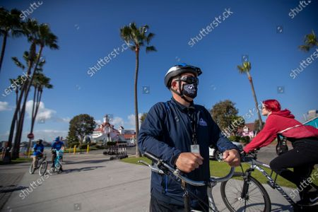 Bikers not wearing masks pass by Long Beach's health ambassadors Chris Bonomo, right center, who has had COVID-19 before and sees the importance in educating and reminding others, Ezequiel Gutierrez, 18, and Pablo Razo, 18, in background at left, as they check on the bike path to make sure people are complying with the current COVID-19 rules and restrictions at Shoreline Village in Long Beach Thursday, Dec. 10, 2020. The city hired 13 youth in partnership with Pacific Gateway Workforce Innovation Network in July to make sure people are following social distancing and mask mandates. They go around busy parks, beaches and streets, handing out masks to people. Long Beach City Council is considering ramping up enforcement for people who are not wearing masks and how it has been handling the pandemic lately, since the city has its own public health department, apart from LA County. The LBPD came under scrutiny recently after the Long Beach Post published a story showing pictures of a police training in early November where dozens of police officers were gathered close together, many not wearing masks. The community ambassadors reminded them about the safer at home order, bringing hand sanitizer, not to come to the park sick, maintain 6 feet distance with people outside of your household, anybody 2 years or older is required to wear a mask, wash hands frequently, and that nobody is allowed to gather with people outside of their household. (Allen J. Schaben / Los Angeles Times)