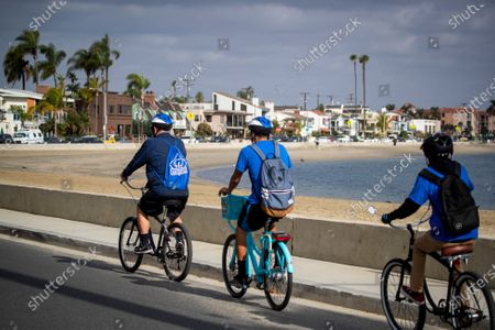 Long Beach's health ambassadors Chris Bonomo, left, who has had COVID-19 before and sees the importance in educating and reminding others, Ezequiel Gutierrez, 18, center, and Pablo Razo, 18, patrol Belmont Shroe along Alamitos Bay to see that people are complying with the current COVID-19 rules and restrictions in Long Beach Thursday, Dec. 10, 2020. The city hired 13 youth in partnership with Pacific Gateway Workforce Innovation Network in July to make sure people are following social distancing and mask mandates. They go around busy parks, beaches and streets, handing out masks to people. Long Beach City Council is considering ramping up enforcement for people who are not wearing masks and how it has been handling the pandemic lately, since the city has its own public health department, apart from LA County. The LBPD came under scrutiny recently after the Long Beach Post published a story showing pictures of a police training in early November where dozens of police officers were gathered close together, many not wearing masks. The community ambassadors reminded them about the safer at home order, bringing hand sanitizer, not to come to the park sick, maintain 6 feet distance with people outside of your household, anybody 2 years or older is required to wear a mask, wash hands frequently, and that nobody is allowed to gather with people outside of their household. (Allen J. Schaben / Los Angeles Times)
