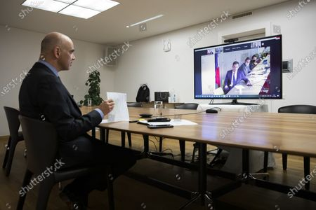 Swiss Federal Councillor and health minister Alain Berset, left, listens to French health minister Olivier Veran, during a virtual meeting with European Ministers on vaccine strategies, in Bern, Switzerland, December 15, 2020.