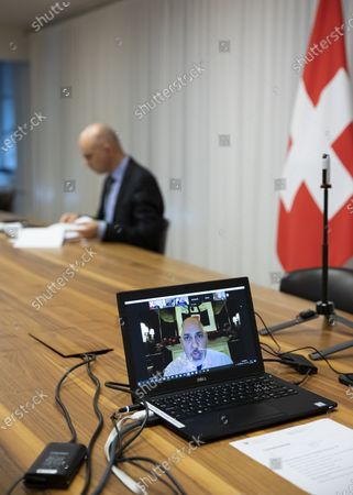 Swiss Federal Councillor and health minister Alain Berset, back, listens to Nadhim Zahawi, British Parliamentary Under-Secretary of State for COVID-19 Vaccine Deployment (displayed on the screen), during a virtual meeting with European Ministers on vaccine strategies, in Bern, Switzerland, December 15, 2020.
