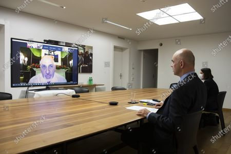Swiss Federal Councillor and health minister Alain Berset, right, listens to Nadhim Zahawi, British Parliamentary Under-Secretary of State for COVID-19 Vaccine Deployment (displayed on the screen), during a virtual meeting with European Ministers on vaccine strategies, in Bern, Switzerland, December 15, 2020.