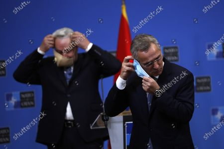 Secretary General Jens Stoltenberg, right, puts on his face mask at the end of a joint press conference with Montenegro Prime Minister Zdravko Krivokapic, left, at the NATO headquarters in Brussels