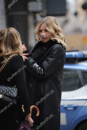 Natasha Stefanenko takes a walk with a friend before leaving in a taxi.