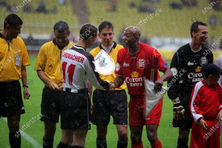 (L to R): Michael Schumacher (GER) Ferrari shakes hands with opposing captain Frankie Fredericks (NAM) former athlete, at the football match. Formula One World Championship, Rd6, Monaco Grand Prix, Preparations, Monte Carlo, Monaco, 17 May 2005. DIGITAL IMAGE