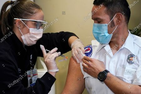 Stock Photo of Seattle Fire Dept. paramedic Alan Goto, right, receives one of the first Pfizer-BioNTech COVID-19 vaccinations by registered nurse Allison Miller at UW Medicine, in Seattle