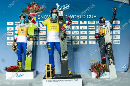 Roland Fischnaller of Italy first place, March Aaron of Italy second place, and Karl Benjamin of Austria celebrate on the podium after the Fis Snowboard World Cup 2021 Men's Parallel Giant Slalom on the Tondi Normale (Faloria) Course in the dolomite mountain range.
