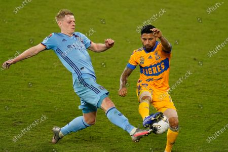New York City FC midfielder Gary Mackay-Steven, left, and Tigres midfielder Javier Aquino battle for the ball during the first half of a CONCACAF Champions League soccer match, in Orlando, Fla