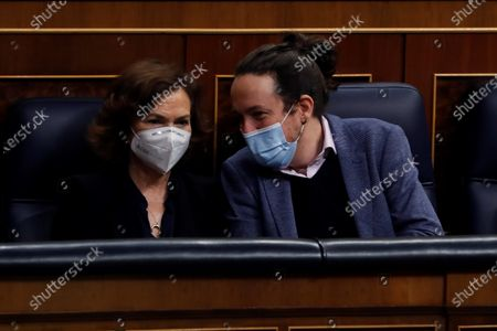 Spanish second deputy Prime Minister, Pablo Iglesias (R), chats with first deputy Prime Minister, Carmen Calvo (L), during a Parliamentary session at the Lower House in Madrid, Spain, where Spanish Prime Minister, Pedro Sanchez, is to inform about the two last EU Councils and the current situation of the coronavirus pandemic in Spain, 16 December 2020.