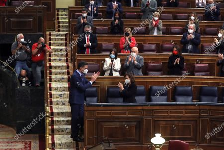 Spanish first deputy Prime Minister Carmen Calvo (C) applaudes Spanish Prime Minister, Pedro Sanchez (C-L), during a Parliamentary session at the Lower House in Madrid, Spain, 16 December 2020, where he is to inform about the two last EU Councils and the current situation of the coronavirus pandemic in Spain.