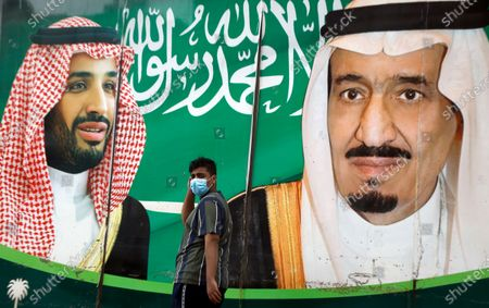 Man wearing a face mask to help curb the spread of the coronavirus walks past a banner showing Saudi King Salman, right, and his son Crown Prince Mohammed bin Salman, outside a mall in Jiddah, Saudi Arabia, . Saudi Arabia plans to cut more than 7% in spending next year, the finance ministry said, as the region's biggest oil producer seeks to trim a gaping budget deficit amid the coronavirus pandemic and falling oil prices