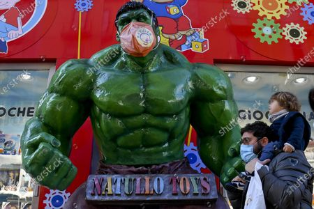 A figure of Marvel Comics character Hulk wearing a protective face mask stands in front of a toy shop in Naples, Italy, 16 December 2020.